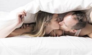 Pár v posteli, bozkávajúc sa pod perinou