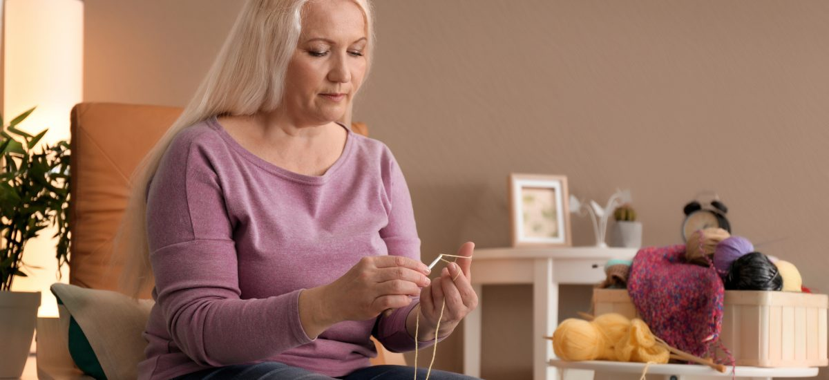 Staršia žena sedí v kresle a štrikuje
