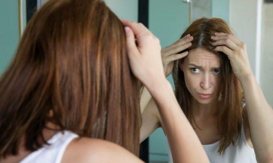 Žena si kontroluje vlasy pred zrkadlom