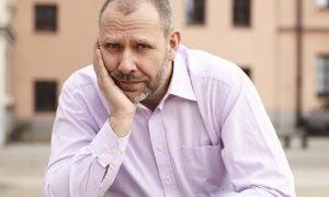 Muž v strednom veku sedí vonku, podopiera si hlavu a pôsobí sklesnuto