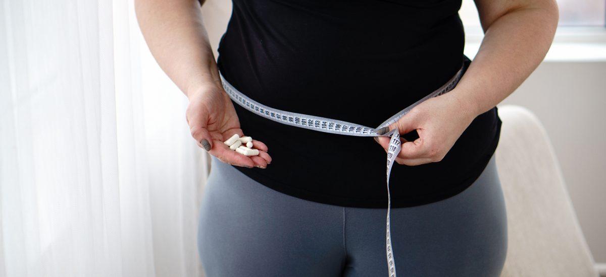 Obézna žena merajúca si pás