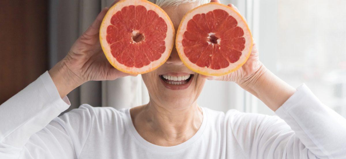 Seniorka držiaca grepy na očiach