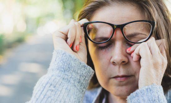 Žena v okuliaroch pretierajúca si oko