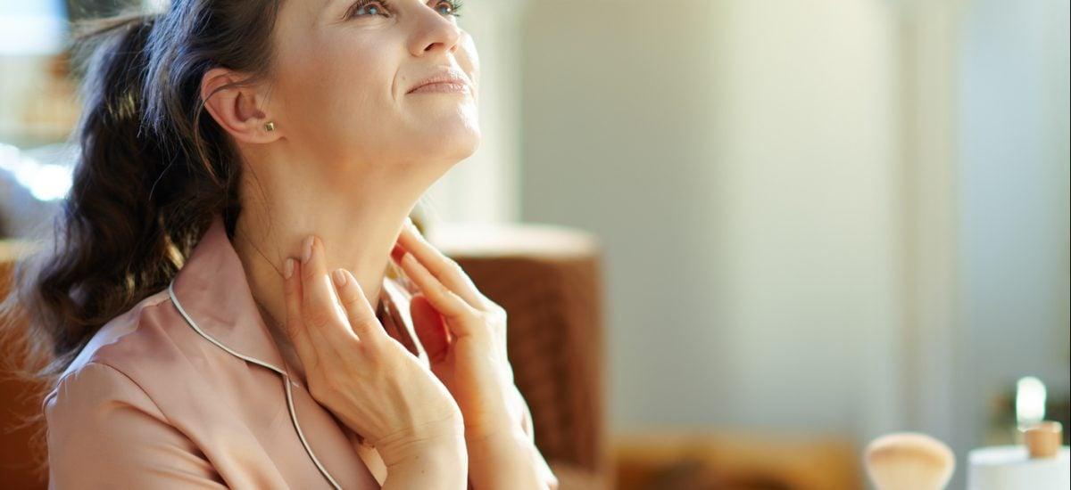 Žena aplikujúca krém na krk
