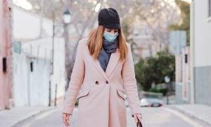 Žena s rúškom na prechádzke so psom