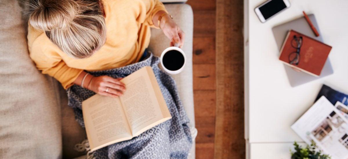 Ležiaca žena číta a pije kávu