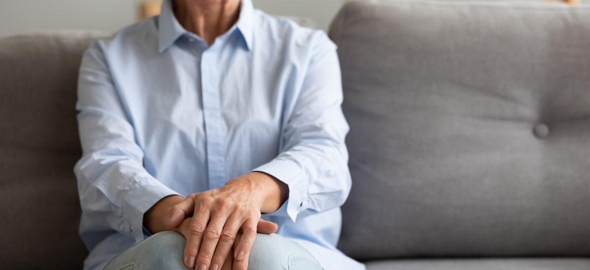 Nešťastná staršia žena sedí sama v depresii na pohovke
