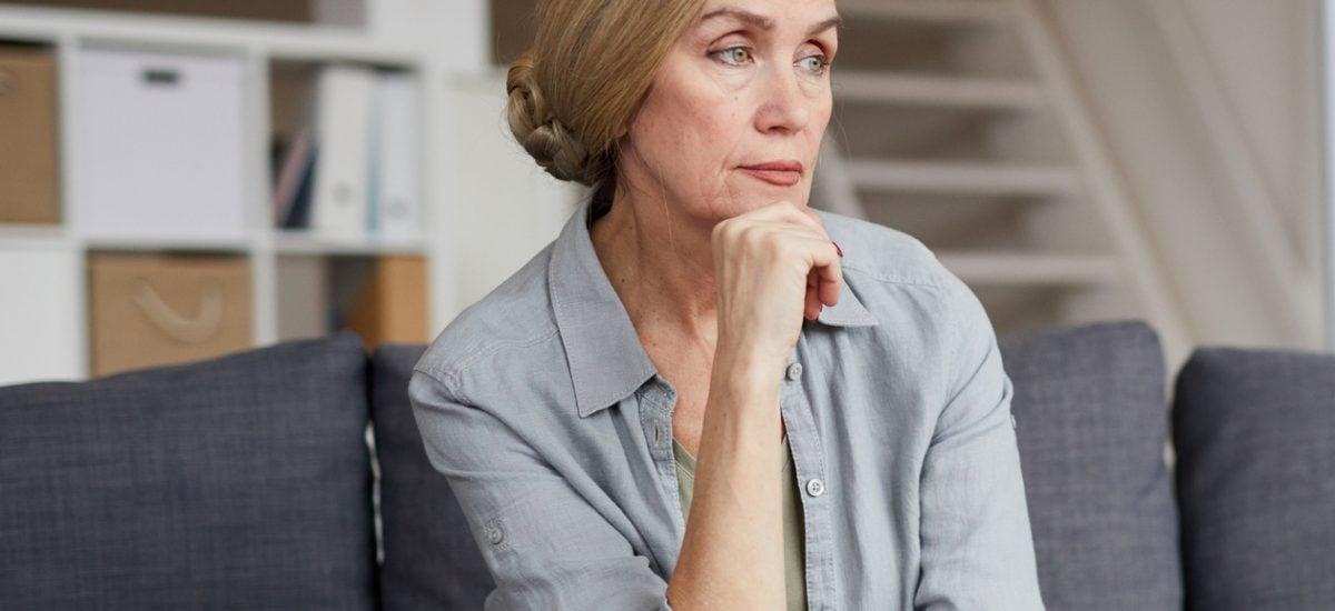 Seniorka sediaca doma na gauči