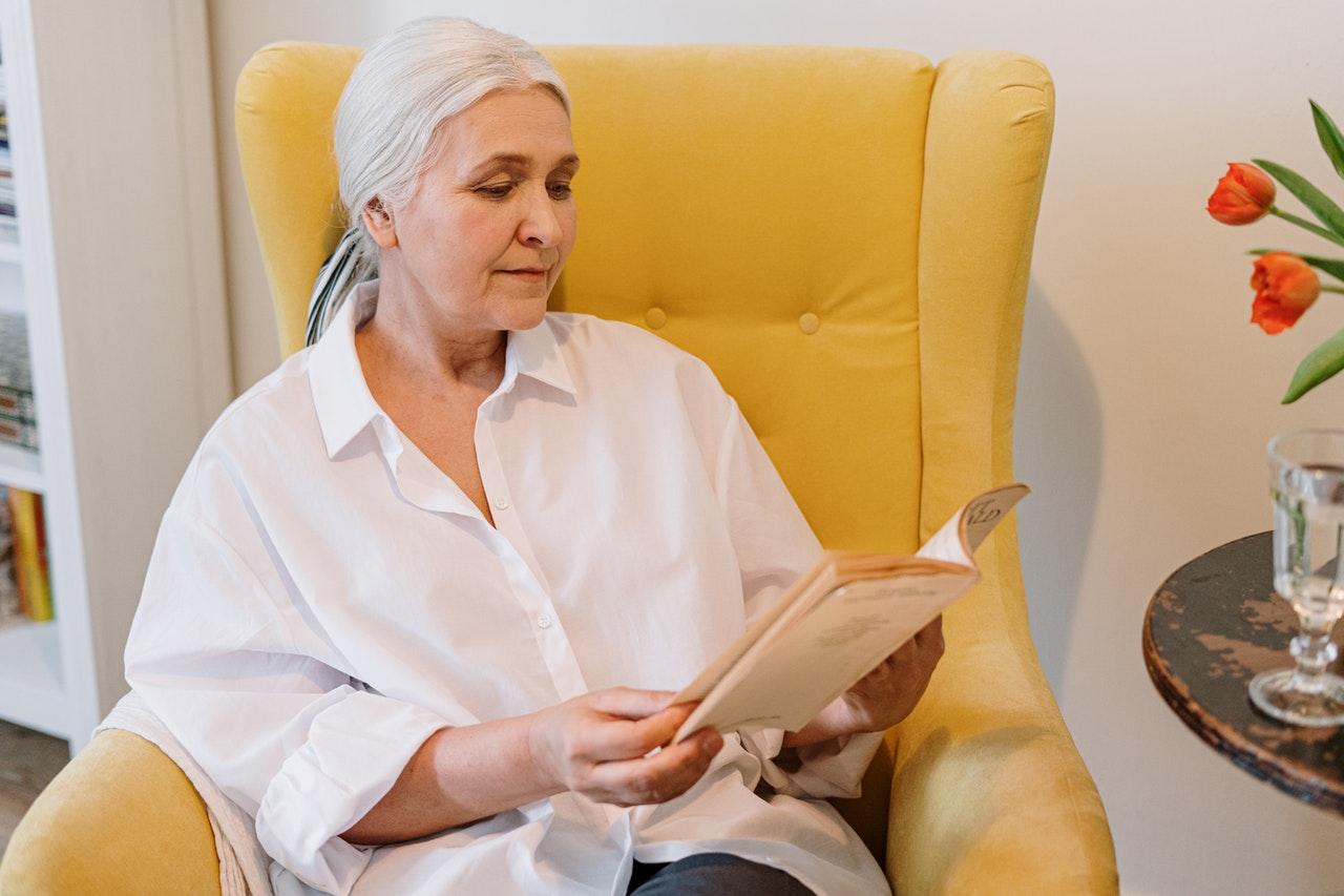 Žena číta knihu v kresle