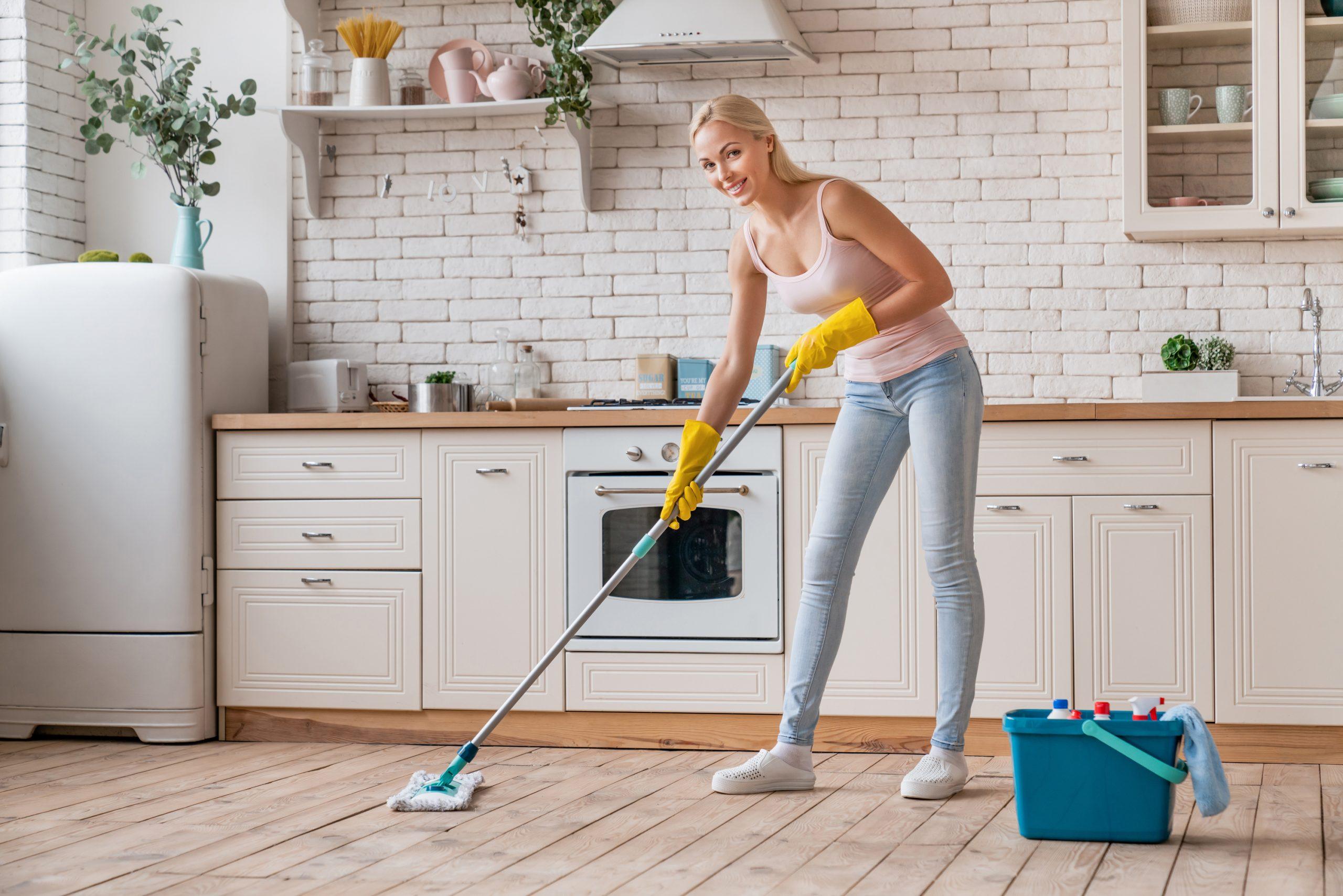 Žena umýva podlahu s mopom v kuchyni.