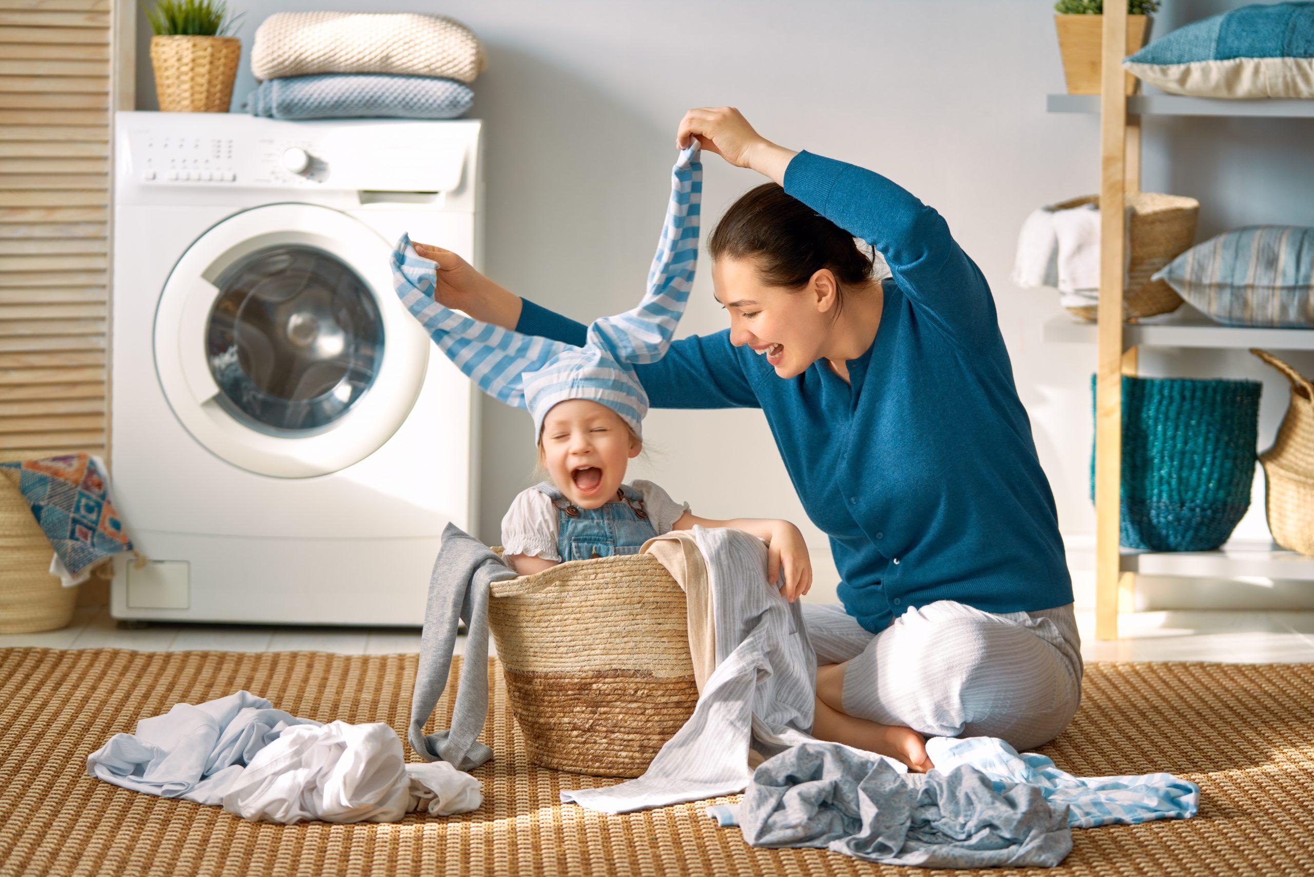 Mladá žena a dieťa v koši na bielizeň pri práčke.