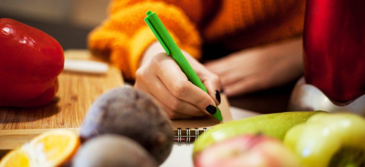 Žena píšuca v kuchyni pri potravinách na stole