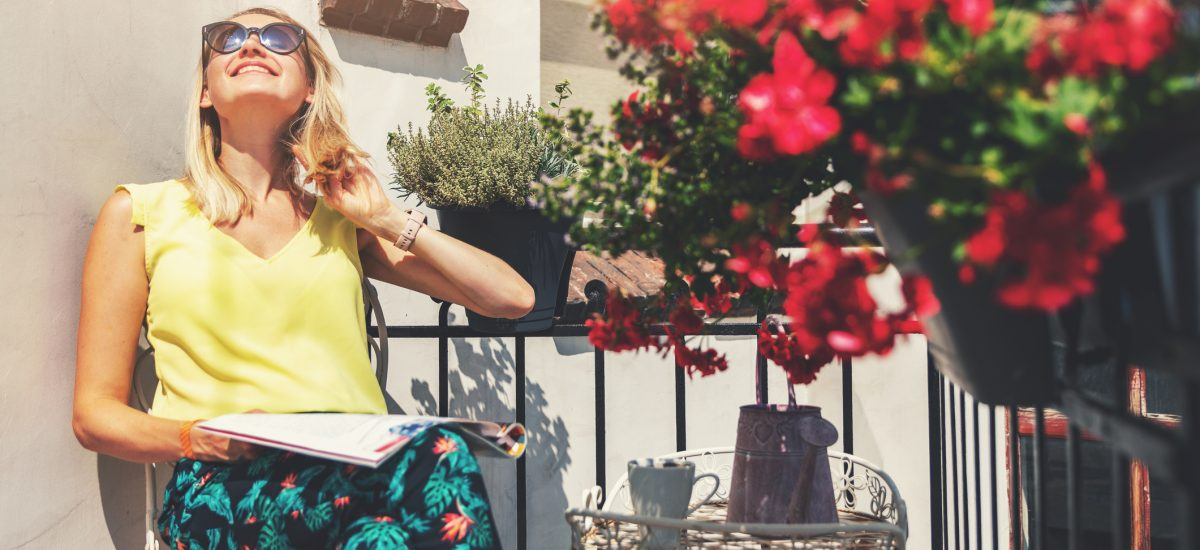 Žena relaxuje na balkóne s kvetmi