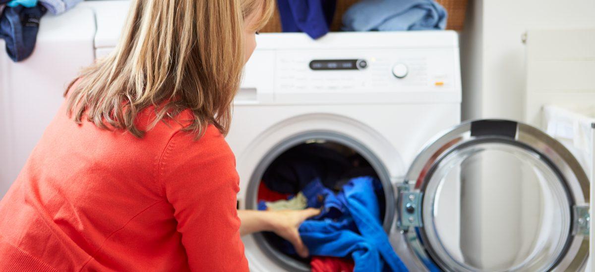 Zadný pohľad na ženu, ktorá plní práčku bielizňou.