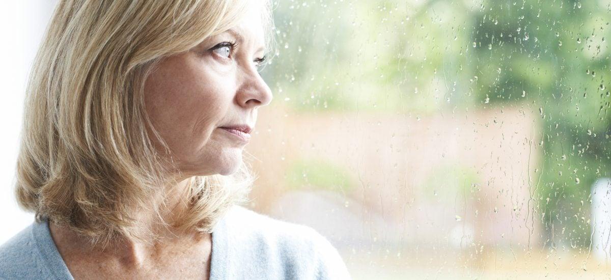 Smutná zrelá žena pozerá von oknom