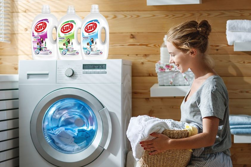 Mladá žena čupí pri práčke s košom bielizne a sleduje prací cyklus, na práčke sú pracie prostriedky SAVO bez chlóru.
