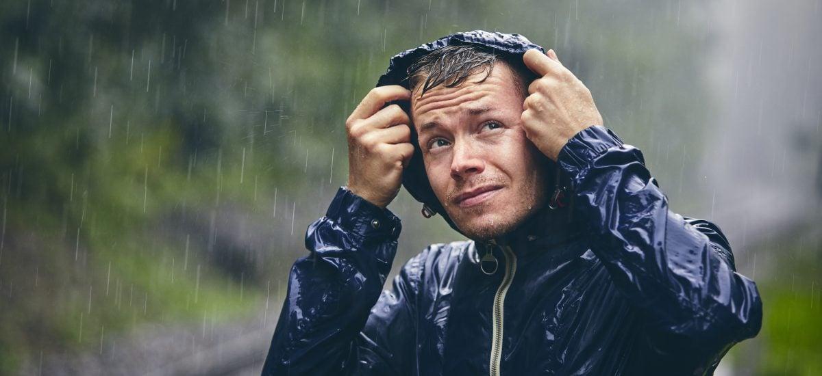 Muž v pršiplášti počas dažďa