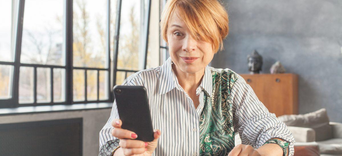 Šokovaná žena s mobilným telefónom v ruke
