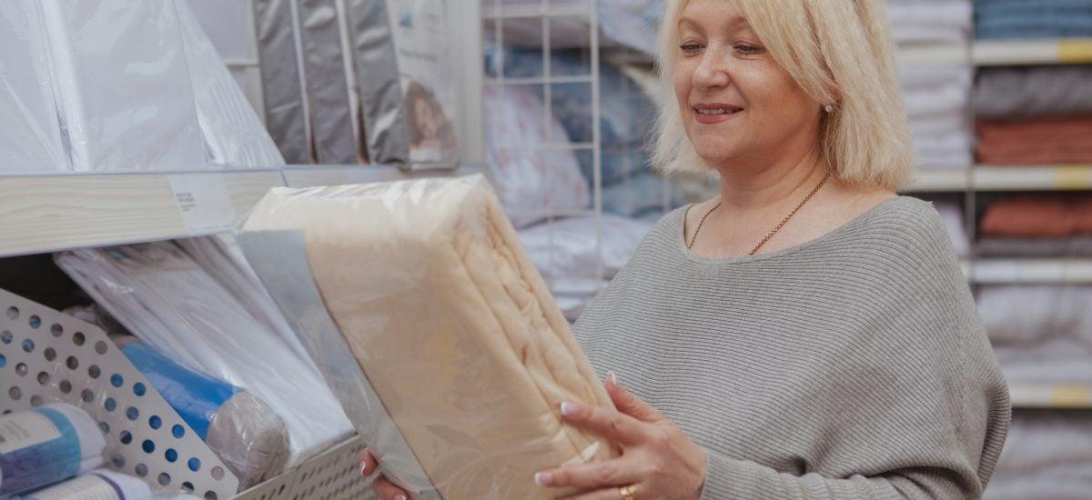 Zrelá žena s balíkom posteľných obliečok