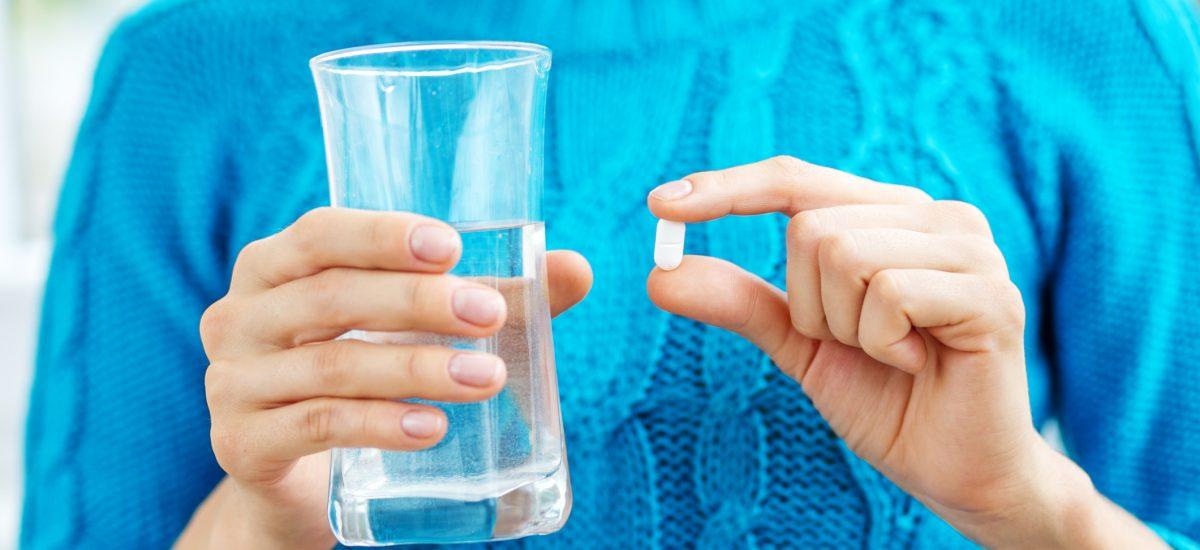 Žena si berie tabletku s vodou