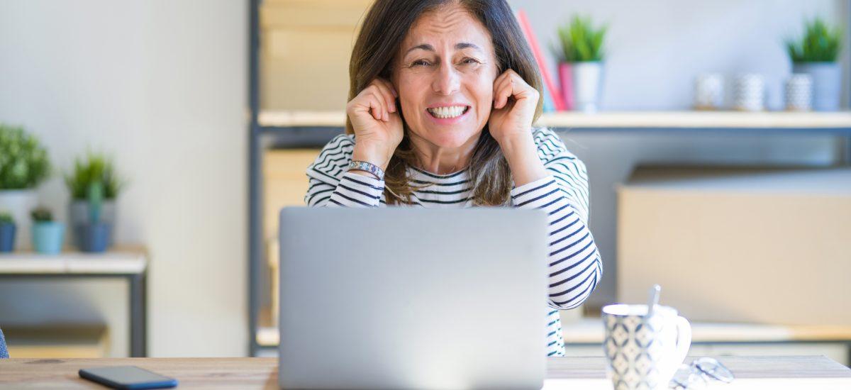 Staršia žena si zakrýva uši pri notebooku