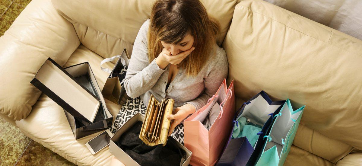 žena na gauči pozerá do peňaženky