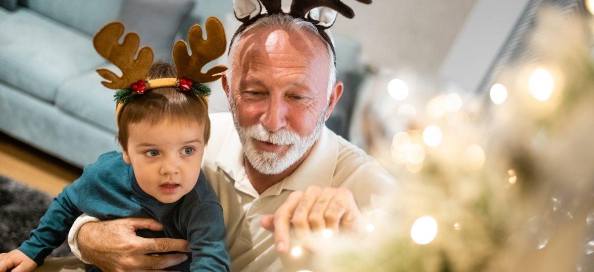 starý otec s vnukom zdobia vianočný stromček