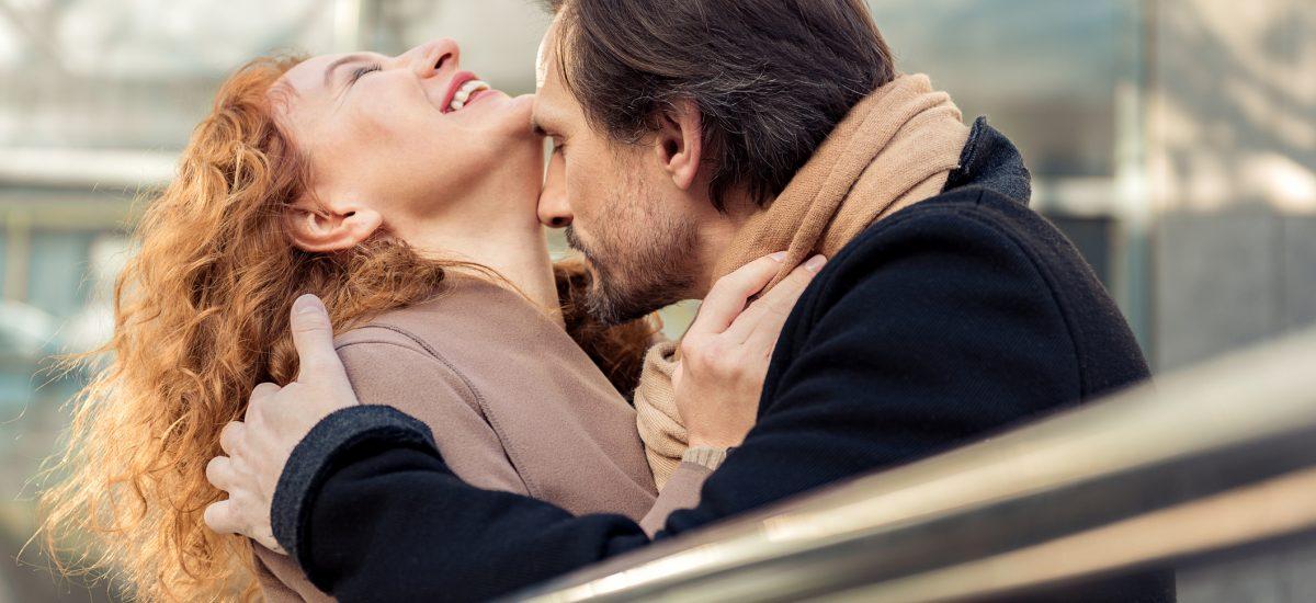 Muž bozkávajúci ženu na krk