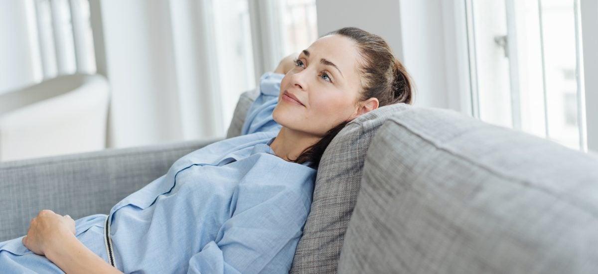 Mladá žena relaxuje na pohovke