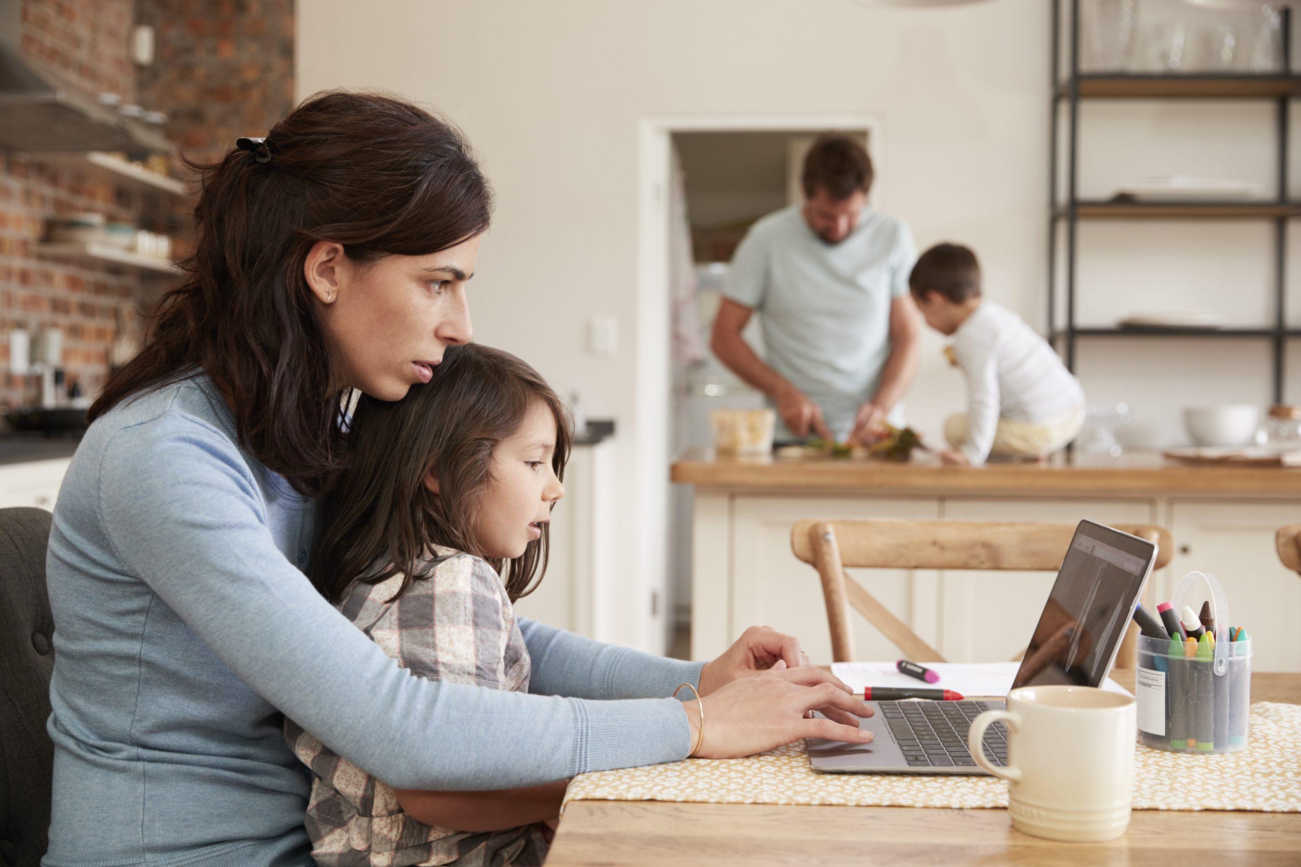 Žena sedí s dieťaťom za stolom pred notebookom.