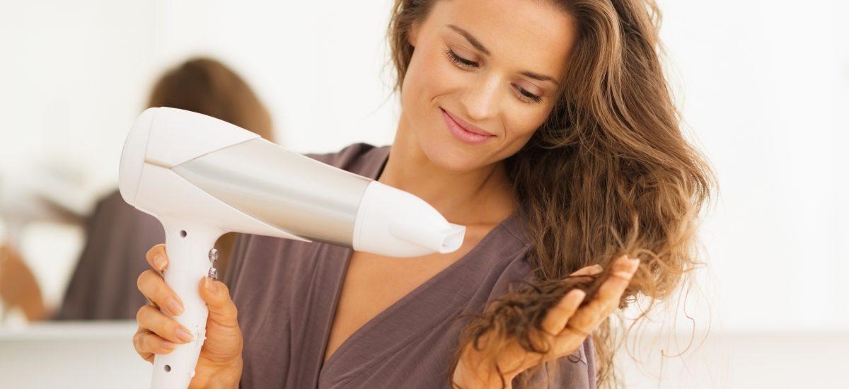 Mladá žena si fénuje vlasy
