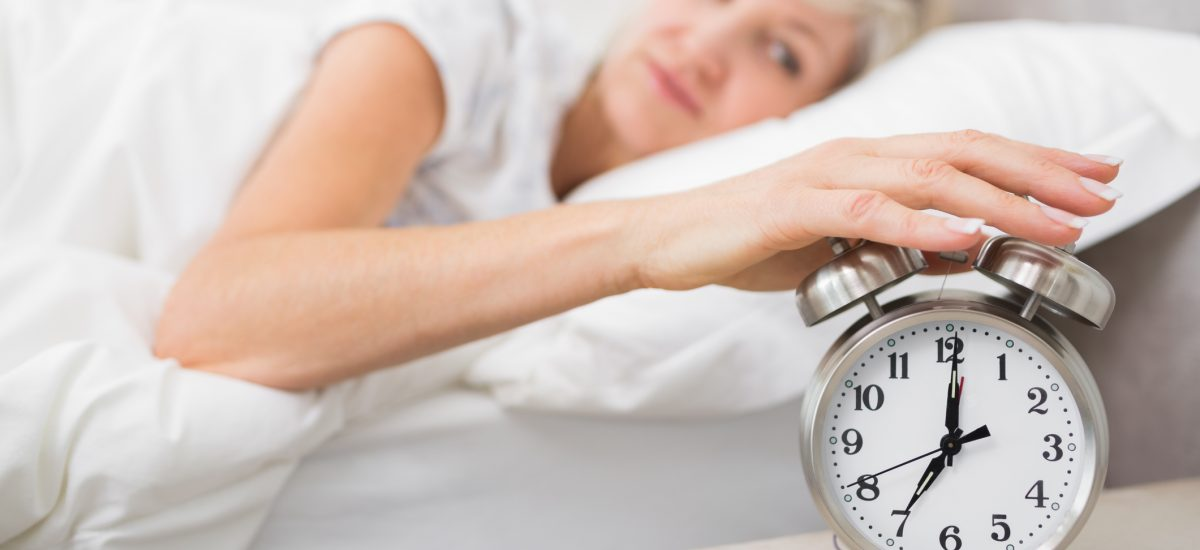 Žena v posteli s budíkom