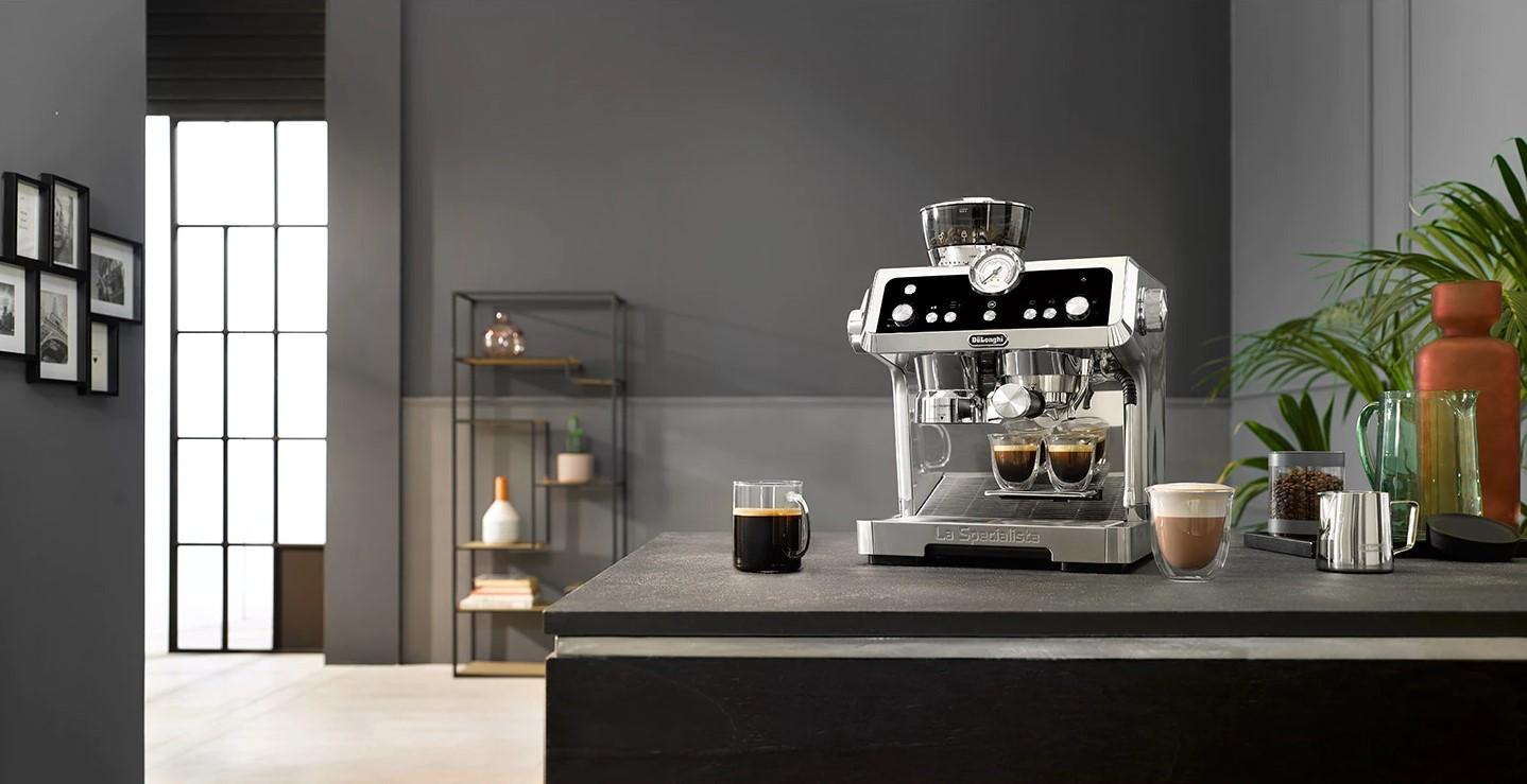 Káva a kávovar deLonghi v kuchyni.