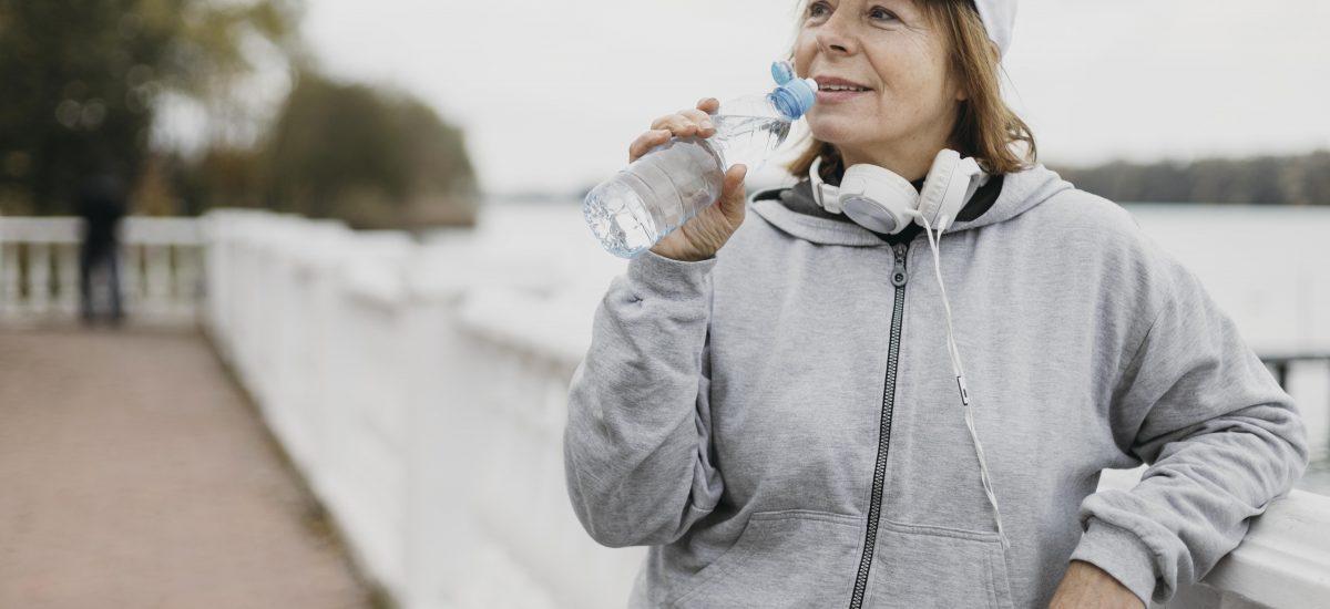 Staršia žena pije vodu z fľaše